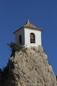 Et kirketårn på toppen af en bjergtop i Guadalest